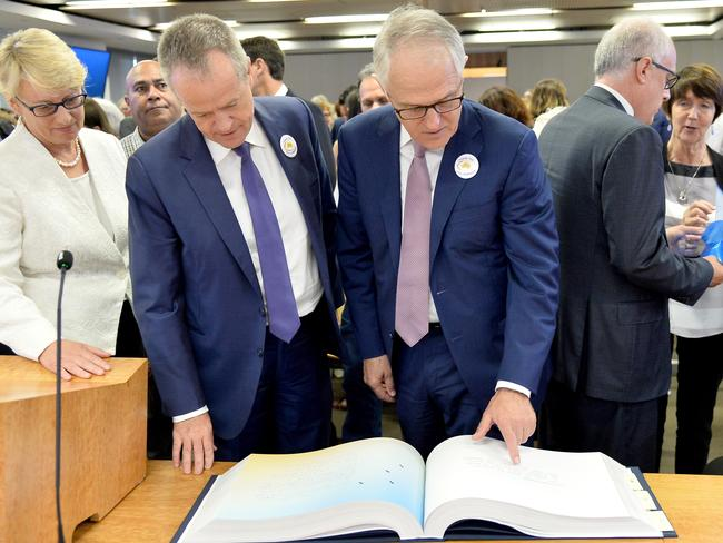 Opposition Leader Bill Shorten and PM Malcolm Turnbull look through the Message to Australia book that was published from handwritten letters from victims of child sexual abuse. Picture: Jeremy Piper