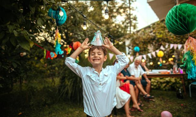 Father carrying smiling birthday boy on a party