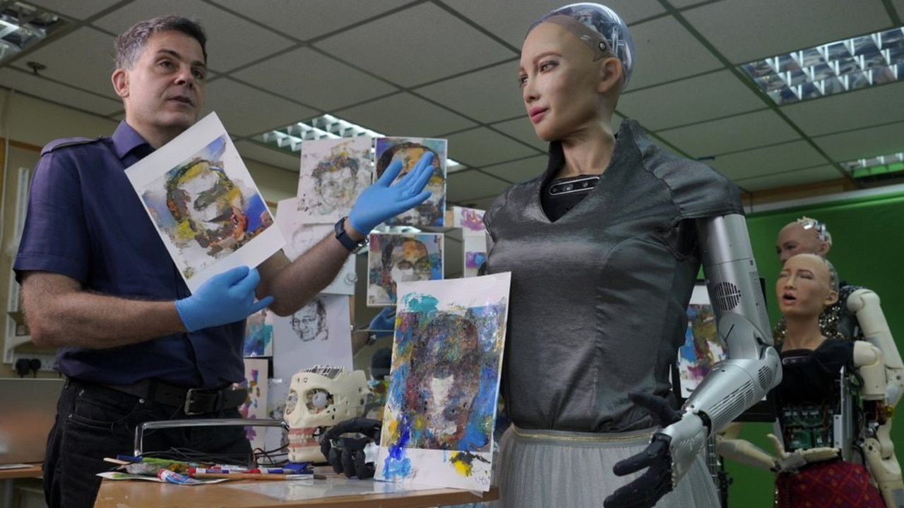 David Hanson, left, creator of Sophia, shows a work of Sophia's at his studio in Hong Kong on March 29, 2021. Picture: AP