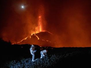 """TOPSHOT - In this handout photograph taken and released by the Spanish Military Emergency Unit (UME) on October 16, 2021, members of the GIETMA (Technological and Environmental Emergencies Intervention Group) of the UME monitor the evolution of a new lava flow, following the eruption of the Cumbre Vieja volcano, on the Canary island of La Palma. - There is no prospect of the volcanic eruption in Spain's Canary Islands ending """"in the short or medium term"""", experts said on October 13, 2021 after three-and-a-half weeks of activity. (Photo by Luismi Ortiz / UME / AFP) / RESTRICTED TO EDITORIAL USE - MANDATORY CREDIT """"AFP PHOTO / LUISMI ORTIZ  / SPANISH MILITARY UNIT (UME) """" - NO MARKETING - NO ADVERTISING CAMPAIGNS - DISTRIBUTED AS A SERVICE TO CLIENTS"""