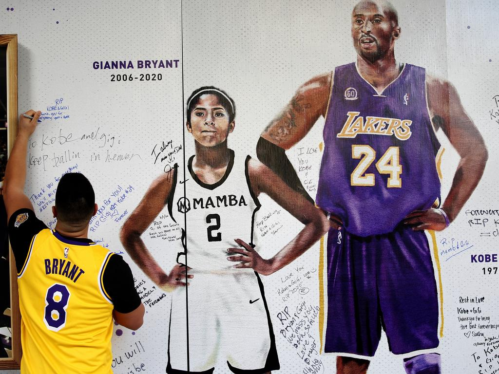 Jesse Reyes Zaragoza writes a message on a memorial display of Kobe Bryant and his daughter, Gianna. Picture: AP