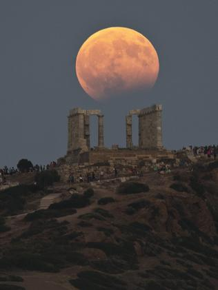 The August full moon rises above the 5th Century BC Temple of Poseidon at Cape Sounio, south of Athens, on Monday, Aug. 7, 2017. More than a hundred of Greece's ancient sites _ but not the Acropolis in Athens _ and museums were kept open until late Monday and concerts organized to allow visitors to enjoy the full moon, which is accompanied by a partial lunar eclipse. (AP Photo/Petros Giannakouris)