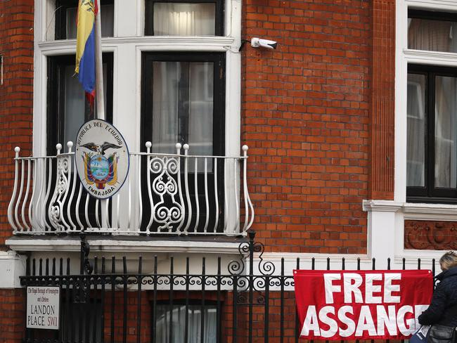 A woman fixes a banner at the Ecuadorean embassy in London. Picture: AP