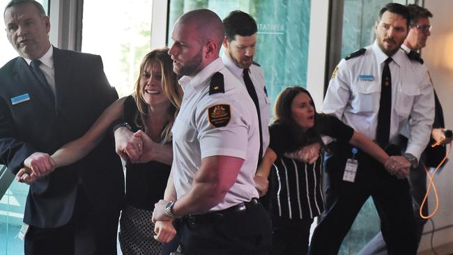 Security guards escort a protester out of the House of Representatives. Picture: Mick Tsikas/AAP