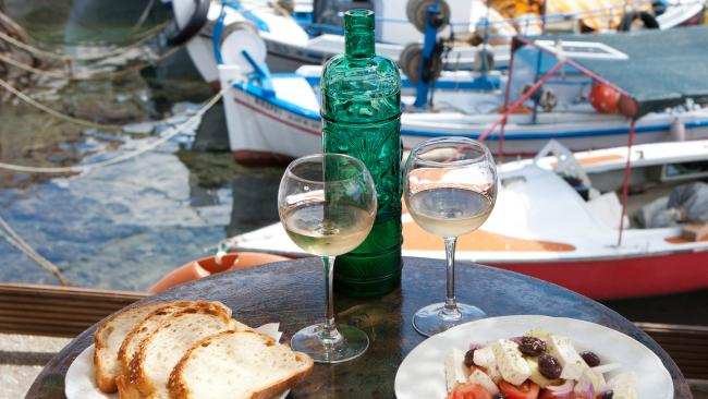 Greece, Agios Nikolaos, traditional Greek starters and wine on table.
