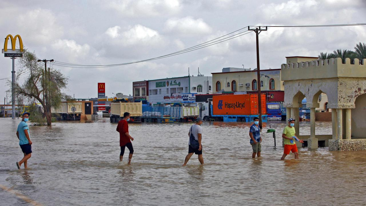 People wade through a flooded street in the northern town of al-Mussanah on October 4. Picture: Mohammed Mahjoub/AFP