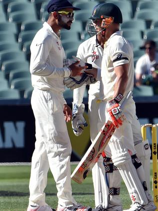 Australia's batsman David Warne (R) talks to India's captain Virat Kohli on the fourth day of the first Test cricket match between Australia and India at the Adelaide Oval on December 12, 2014. AFP PHOTO / SAEED KHAN IMAGE RESTRICTED TO EDITORIAL USE - STRICTLY NO COMMERCIAL USE