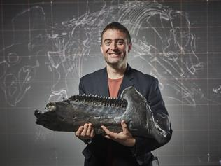 Dr Erich Fitzgerald holding a 3D replica of the Triceratops mandible (jaw bone). Photographer - Benj