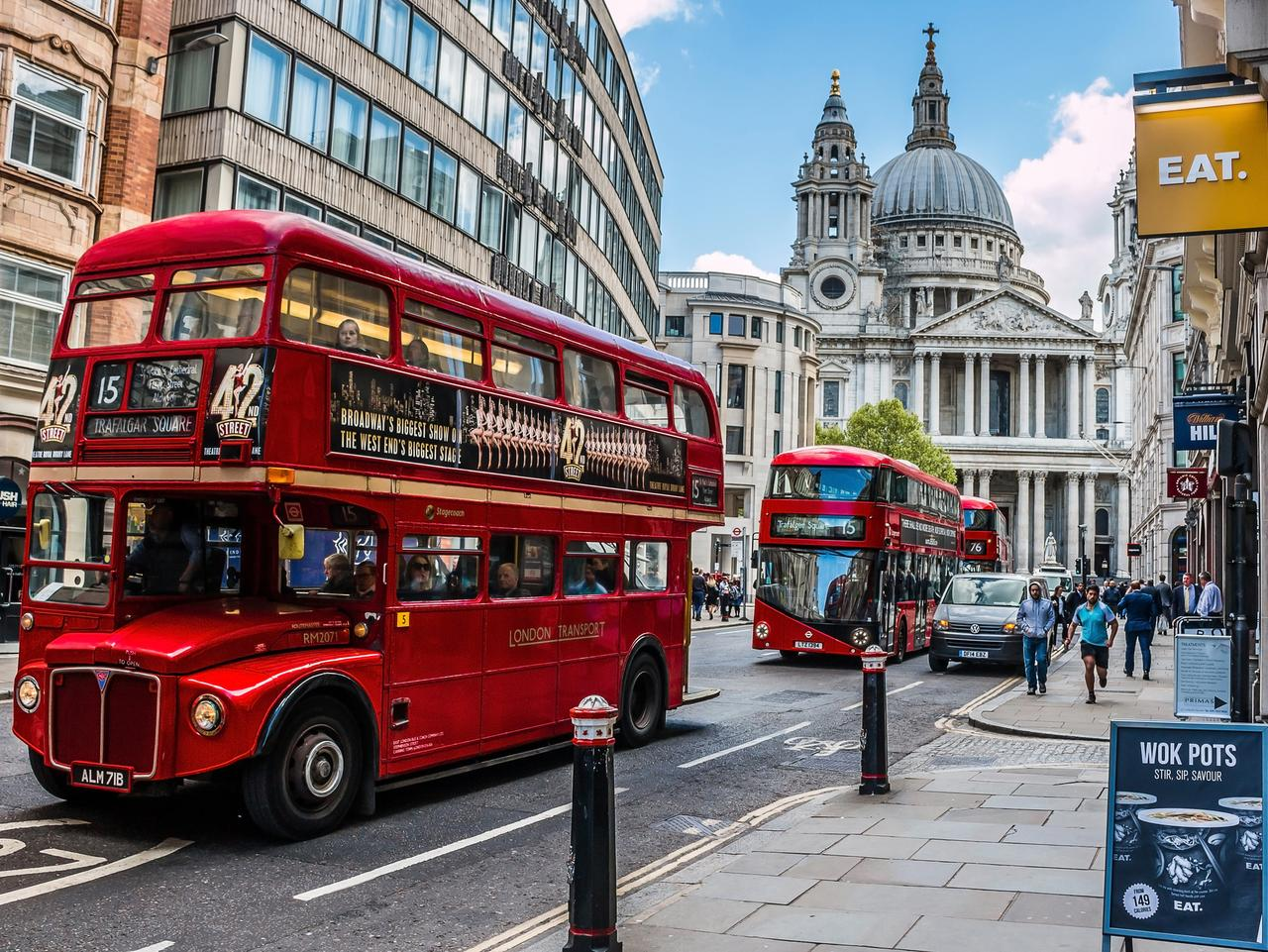 London: Busy street in central London, with classic retro and new modern double decker buses and St. Paul's Cathedral in the background. HDR style image