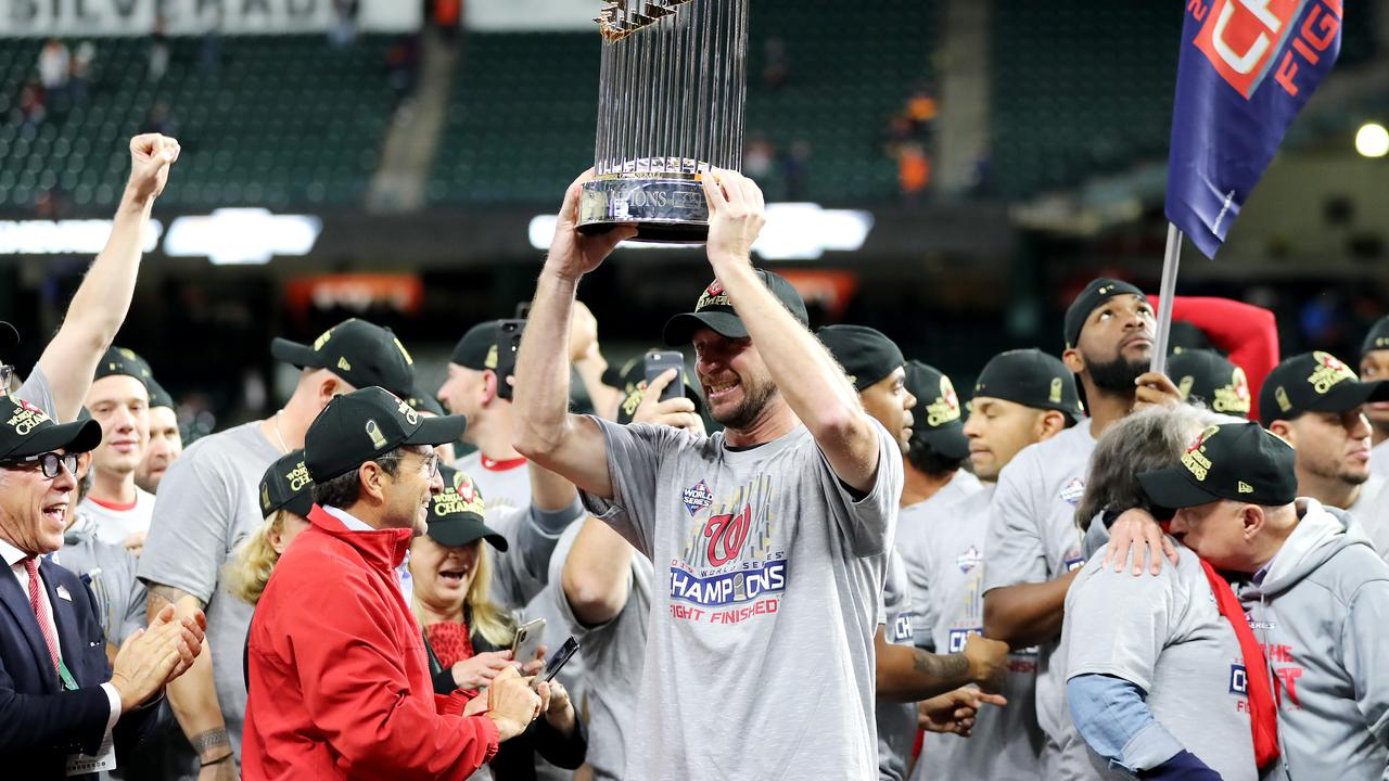 Max Scherzer #31 of the Washington Nationals holds the Commissioners Trophy after defeating the Houston Astros 6-2 in Game Seven to win the 2019 World Series.
