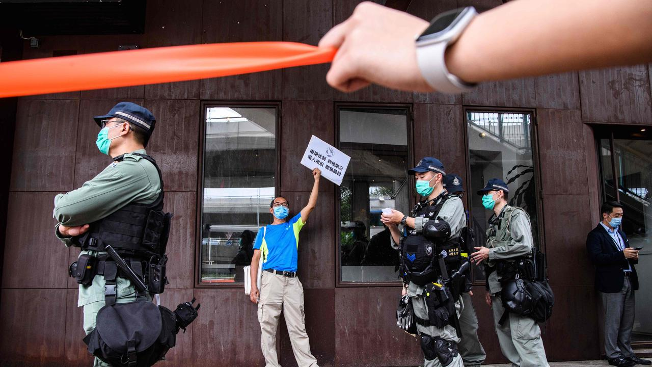 Riot police stand guard near a pro-democracy protester on Friday. Picture: Anthony Wallace/AFP