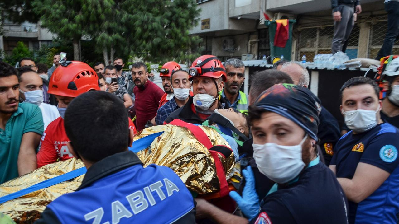 Rescuers and local volunteers carry a wounded victim from a collapsed building in Izmir. Picture: AFP.