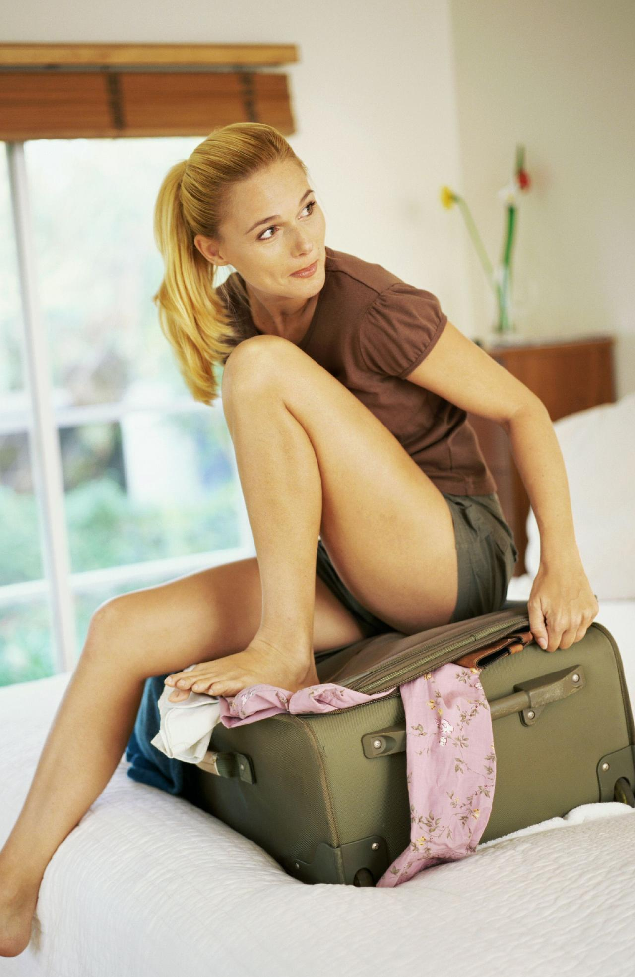 Young woman sitting on a suitcase full of clothes