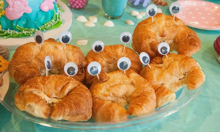 "Crab croissants - Every little mermaid needs their crab companion, right? Adding googly eyes to croissants means everyone can have their own Sebastian! Fill them with ham and cheese and it's a great savoury party treat.  <br />Source: <a href=""http://allthatglittersisgold.net/2014/06/03/a-mermaid-birthday-party/"">All That Glitters Is Gold</a> <br />"