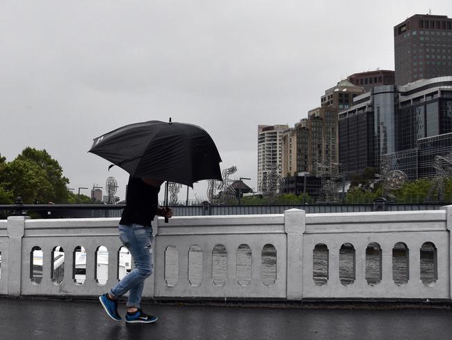 A man crosses Queensbridge in Melbourne in wet weather yesterday. Picture: Julian Smith, AAP
