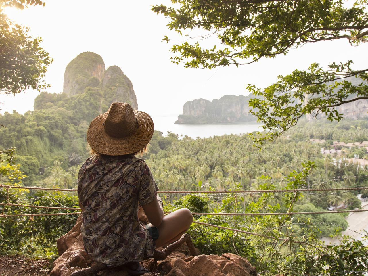 Man with sun hat, looking at view of Railay Beach, Krabi, Thailand
