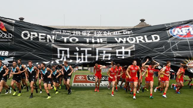Port Adelaide and Gold Coast players run through a joint banner. Picture: AFL Media