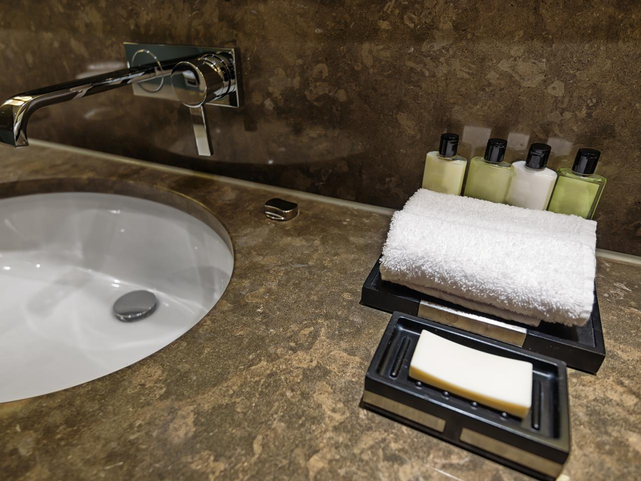 Hotel bathroom detail with soap, towel and shampoo