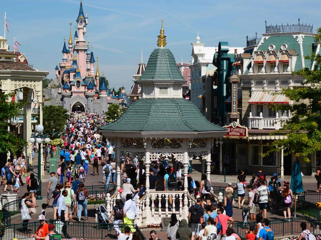 (FILES) This file photo taken on August 06, 2015 shows visitors walking down the Main Street of Disneyland Paris in Marne-la-Vallee. A decision will be given on June 23, 2017, about three ex-employees of Eurodisney trialed for misappropriation of funds. / AFP PHOTO / Bertrand GUAY
