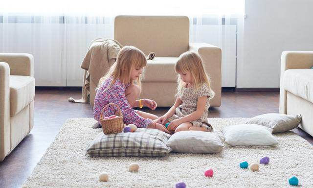 Calm pretty sisters sitting on carpet and playing with Easter eggs counting and passing them in living room
