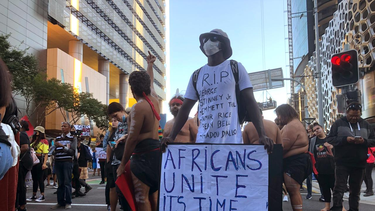 A man holds a sign in solidarity with thousands of people marching during a Black Lives Matter protest in Brisbane on Saturday, June 6. Picture: John Pye