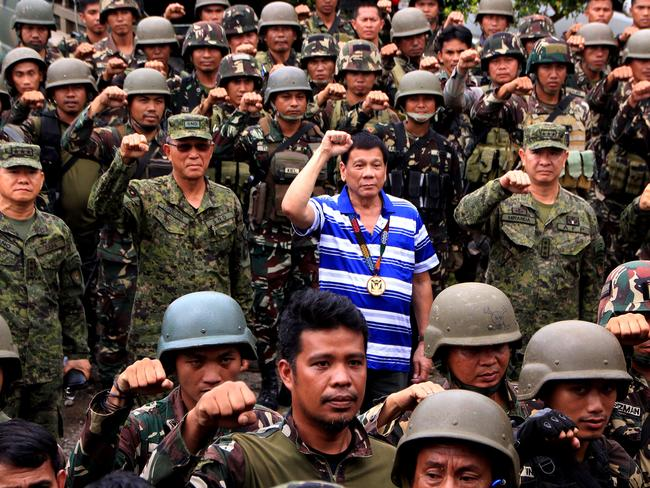 Philippine President Rodrigo Duterte (C) raises a clenched fist with military top brass as he visits troops in Nanagun, Lombayanague in Lanao del Sur in Mindanao island, were soldiers are waging war with Islamic State group sympathisers. Picture: AFP / Richel Umel