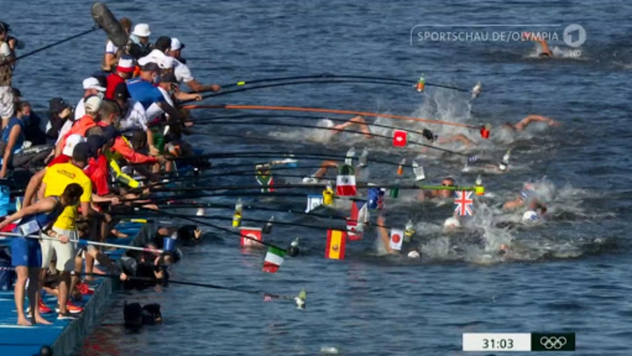 Swimmers are offered drinks as they pass the fuel station.