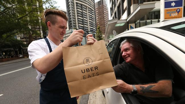 Esquire chef Gus Baker hands Uber driver Michael Helen a restaurant lunch to deliver in Brisbane. Picture: Lyndon Mechielsen