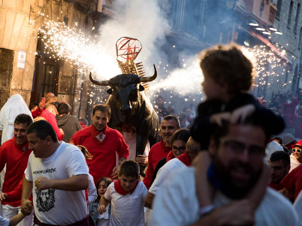 """A man in a """"Toro de Fuego"""" (bull of fire) costume chases people during day four of Spain's controversial Running of the Bulls festival. Picture: Jaime Reina/AFP"""