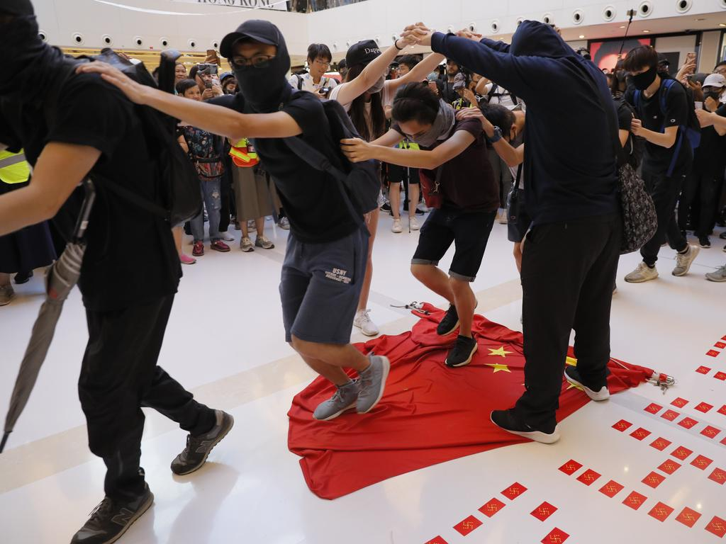 Protesters step on a Chinese national flag during a protest at a mall in Hong Kong. Picture: AP