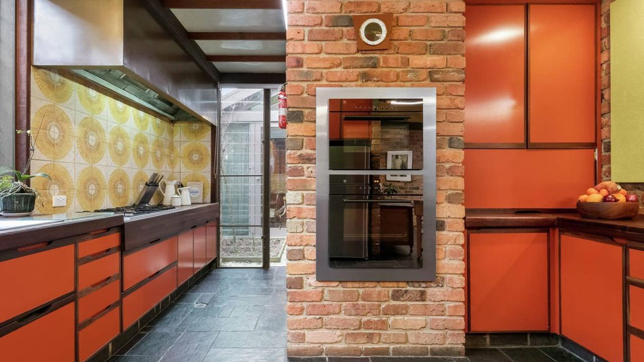 The kitchen has retro tiles and cabinets.
