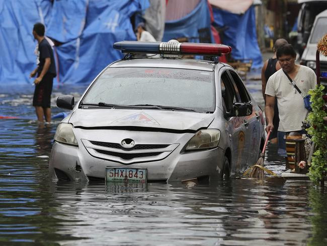 A police car is parked along a flooded street caused by rains from Typhoon Nock-Ten as vendors selling handicrafts including Christmas decorations clean rubbish in Quezon City, north of Manila.