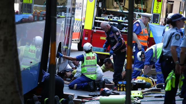 Paramedics and police worked to save Christine Mullholland after she was trapped by the bus. She later died despite their best efforts.