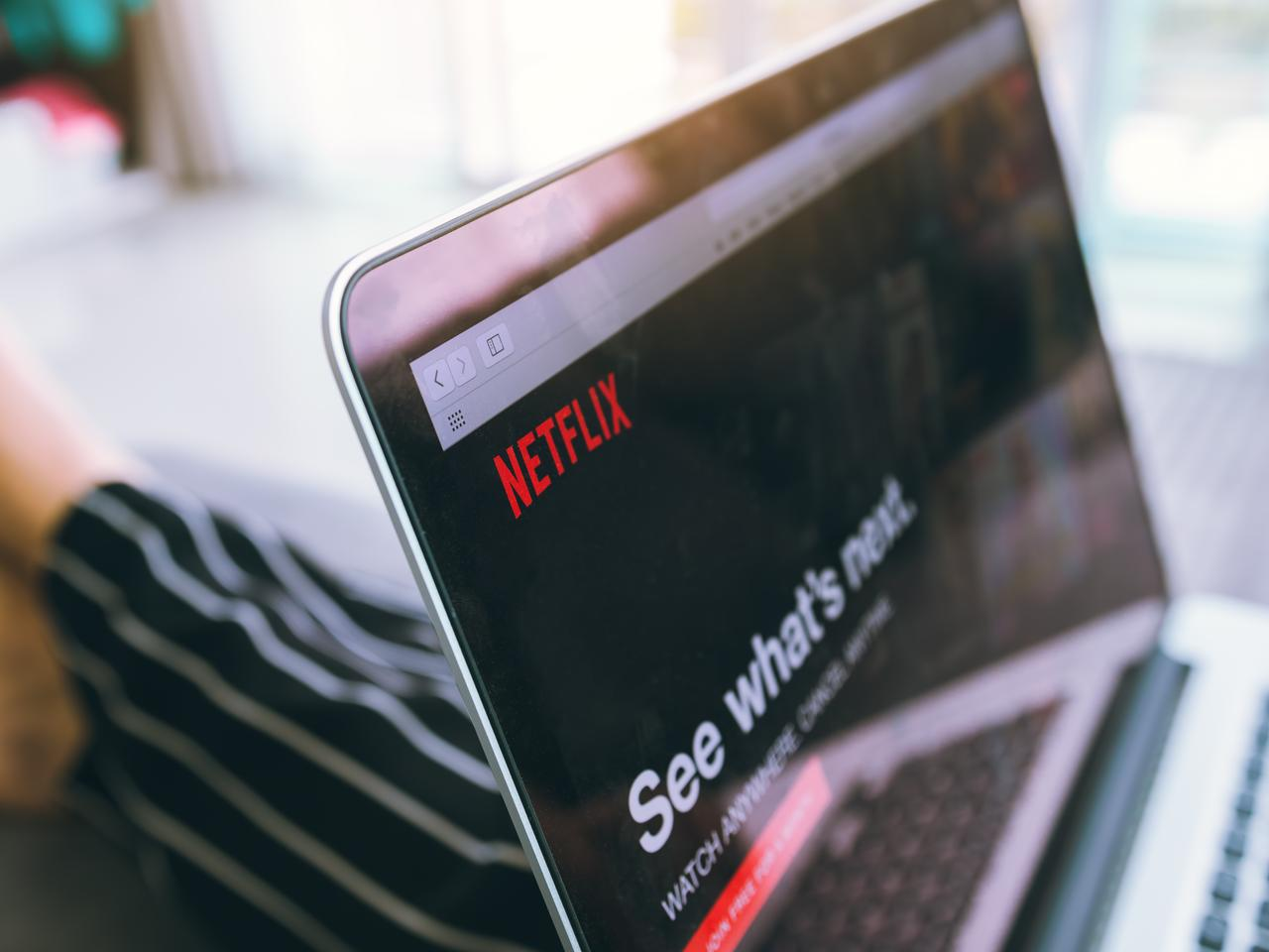 Close up of man sitting with laptop, with Netflix website on screen.