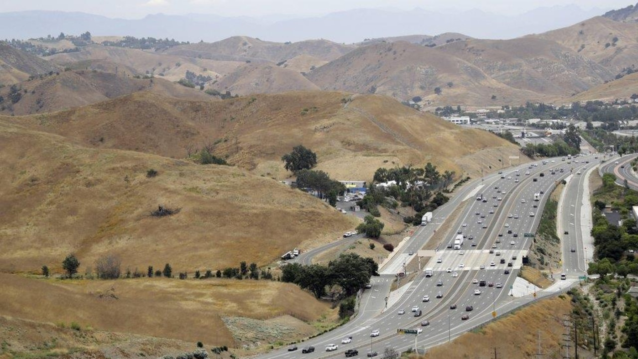 In this July 25, 2019, photo, U.S. Highway 101 passes between two separate open space preserves on conservancy lands in the Santa Monica Mountains in Agoura Hills, Calif. Hoping to fend off the extinction of mountain lions and other species that require room to roam, transportation officials and conservationists will build a mostly privately funded wildlife crossing over this freeway. It will give big cats, coyotes, deer, lizards, snakes and other creatures a safe route to open space and better access to food and potential mates. (AP Photo/Marcio Jose Sanchez)