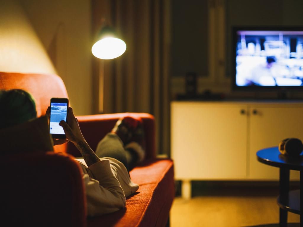 Watching TV while scrolling on a mobile phone is common in most households these days. Picture: istock