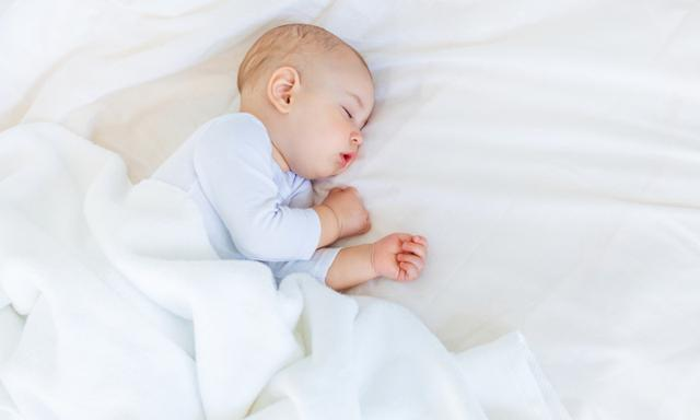Close-up portrait of adorable baby boy sleeping in bed, 1 year old baby concept
