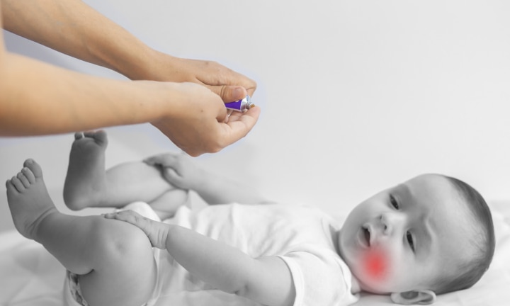 Baby boy teething pain. Little 6-month baby having teeth pains. Mother rubbing gel to her little baby boy's teeth. Medicine and health concept.