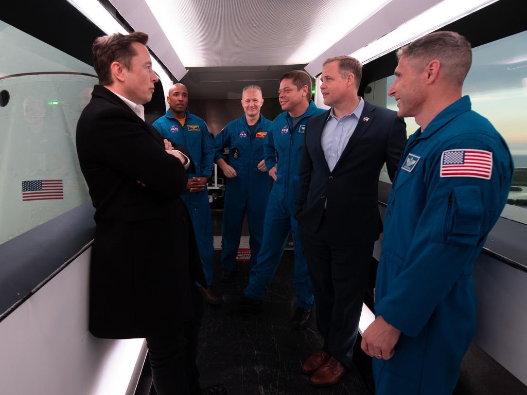 SpaceX CEO and Chief Designer Elon Musk, left, with NASA astronauts Victor Glover, Doug Hurley, Bob Behnken, NASA Administrator Jim Bridenstine, and NASA astronaut Mike Hopkins seen inside the crew access arm. Picture: Joel KOWSKY/NASA/AFP