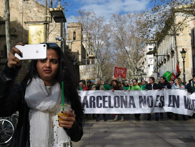 """A tourist takes a selfie in front of a banner that says """"Barcelona is not for sale"""" during a demonstration in Barcelona on January 28, 2017. Photo: AFP PHOTO/LLUIS GENE"""