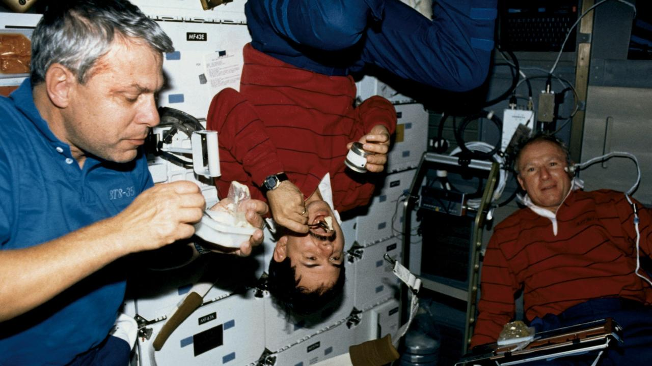 Undated. NASA astronauts Robert Parker, Ronald Parise and Vance Brand aboard the space shuttle prove that you don't need a table and chairs to enjoy eating in earth's orbit. Picture: NASA (no copyright applies)