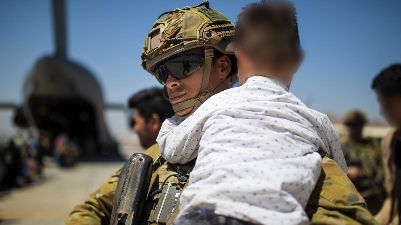 An Australian Army soldier, part of the 1st Battalion, Royal Australian Regiment ready combat team carries an Afghan child while assisting a family aboard the RAAF C-17A Globemaster at the Hamid Karzai International Airport. *** Local Caption *** The Ready Combat Team including members of the 1st Battalion, the Royal Australian Regiment, have been working with Australian Government officials from the Department of Foreign Affairs and Trade, Department of Home Affairs and Australian Border Force to identify, collect and assist Australian nationals and approved foreign nationals enter Hamid Karzai International Airport at Abbey Gate.