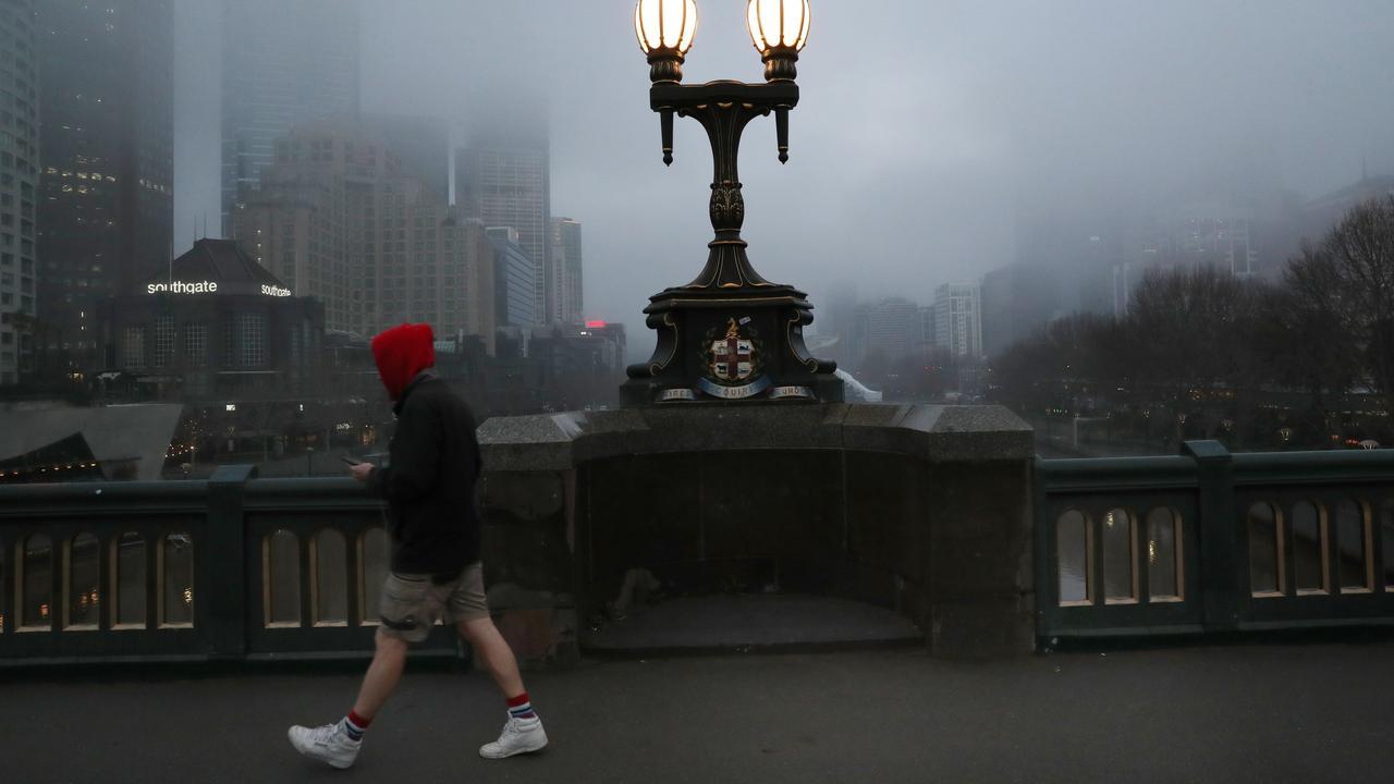 A pedestrian walks across Princes Bridge as thick fog hangs over Melbourne. Picture: David Crosling