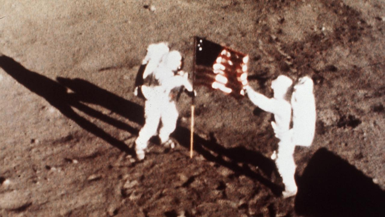 """Apollo 11 astronauts Neil Armstrong and Edwin E. """"Buzz"""" Aldrin, the first men to land on the moon, plant the US flag on the lunar surface. Picture: AP/NASA"""