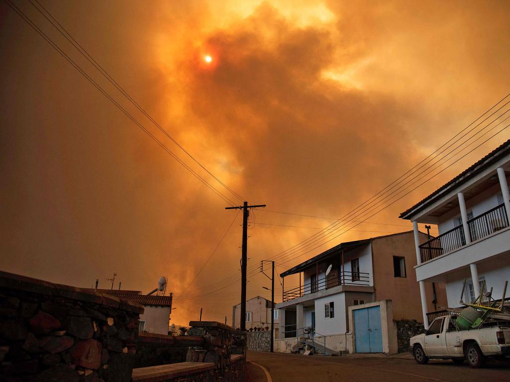 Heavy smoke covers the sky above the village of Ora in the southern slopes of the Troodos mountains, as a giant fire rages on the Mediterranean island of Cyprus. Picture: AFP