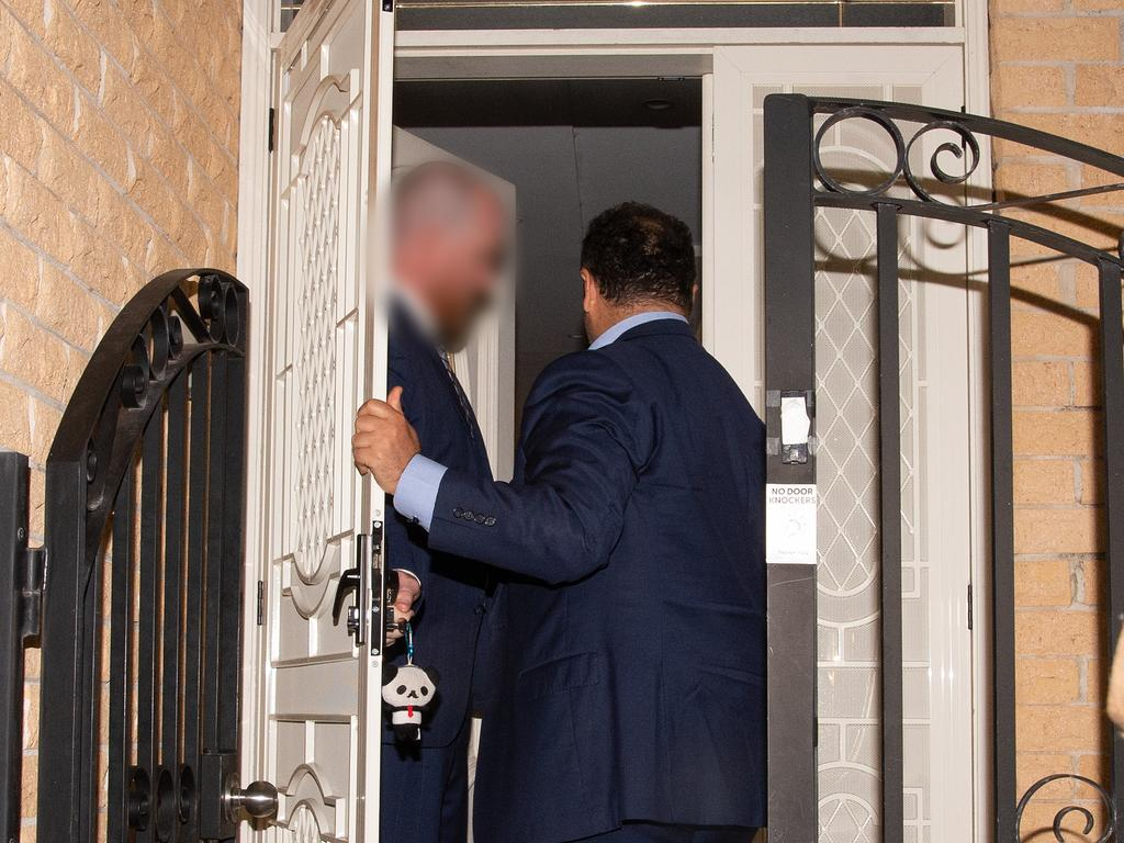 NSW Labor MP Shaoquett Moselmane is greeted by federal agents as he arrives at his Rockdale home in Sydney on Friday night. Picture: AAP