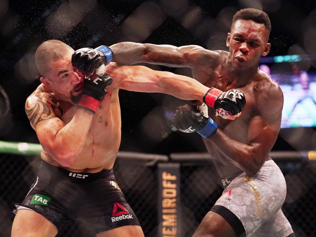 *This picture has been selected as one of the Best of the Year Sports images for 2019*  Robert Whittaker of Australia is hit by Israel Adesanya of New Zealand as they compete during UFC 243 at Marvel Stadium in Melbourne, Sunday, October 6, 2019. (AAP Image/Michael Dodge) NO ARCHIVING,EDITORIAL USE ONLY