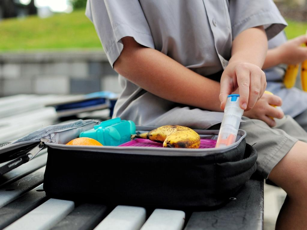 Young boy with a packed lunch takes out his anaphylaxis auto injector.
