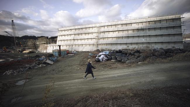 A woman walks near sea walls being built in Rikuzentakata, Iwate Prefecture, northeastern Japan.