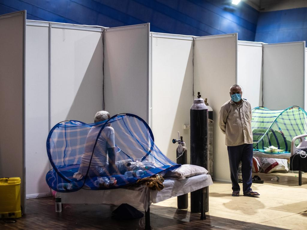 A patient sits on a bed inside a makeshift covid care facility in a sports stadium at the Commonwealth Games Village in New Delhi. (Photo by Getty Images/Getty Images)